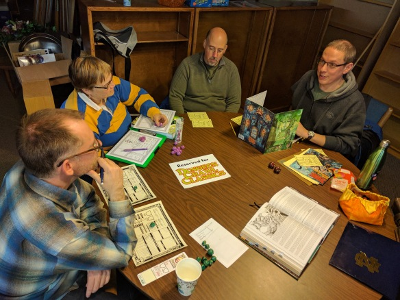 Four people, with dice, pencils, and paper, gathered around a table ready to play Dungeon Crawl Classics.