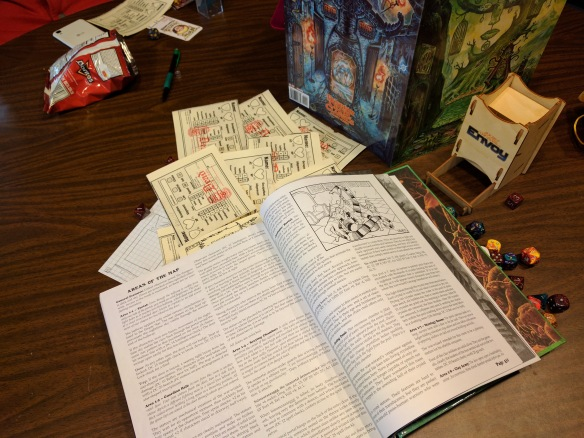 The DCC RPG book open, character sheets, dice, and judge's screen