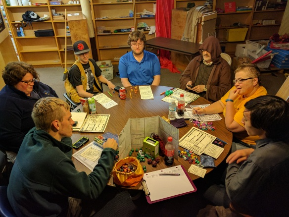 7 people gathered around a table with character sheets, books, and dice.